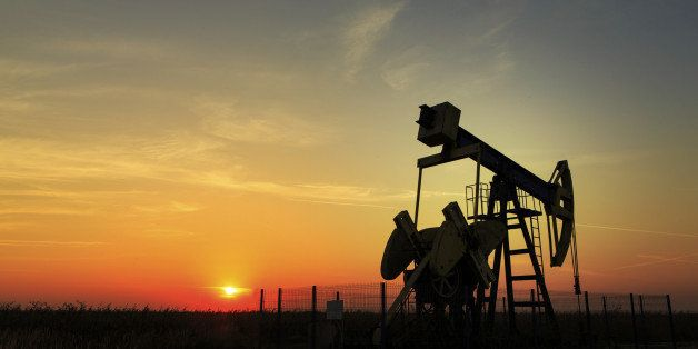 Operating oil and gas well profiled on sunset sky