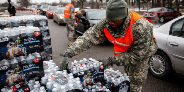 FLINT, MI - JANUARY 21:  Army National Guard Specialist David Brown loads bottled water into waiting cars at a fire station o