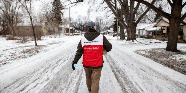 FLINT, MI - JANUARY 21:  American Red Cross volunteer John Lohrstorfer walks down Maryland St. on Flint's north side to deliv