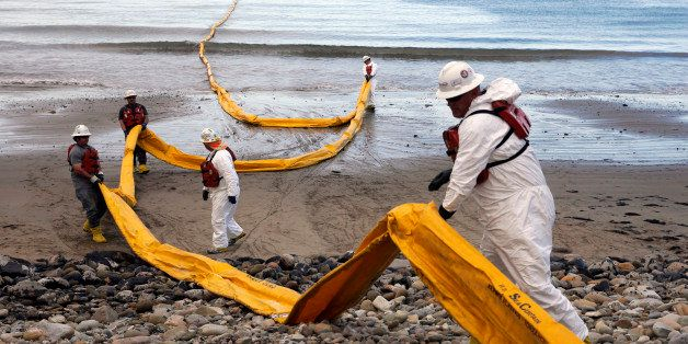 FILE - In this May 21, 2015, file photo, workers prepare an oil containment boom at Refugio State Beach, north of Goleta, Cal