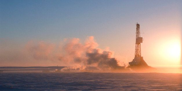 Oil drilling north of the Arctic Circle near Tuktoyaktuk, Northwest Territories, Canada with the sun rising up at dawn