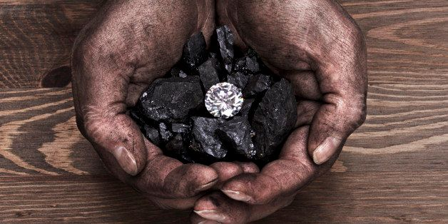 A miners hands holding a solitaire diamond in amongst pieces of coal.