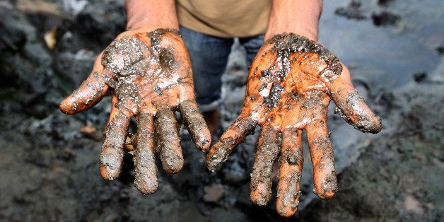 Eric Dooh, a farmer, shows the oil polluted mud from his fish ponds affected by an oil spill in 2004 in Goi, Nigeria, on Wedn