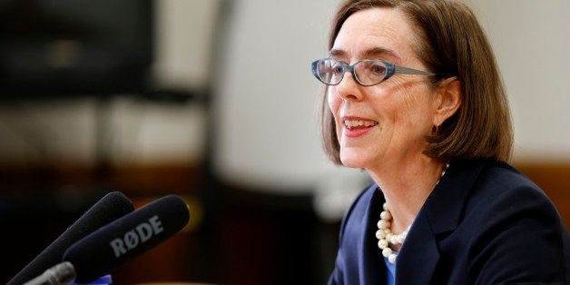 Gov. Kate Brown talks with members of the media to preview  legislation for the upcoming session at the Capitol Building, in