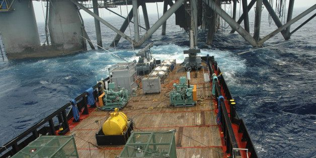 Air guns blast at the stern of a work vessel alongside an offshore oil rig. The air guns are deployed by cranes. Air compress