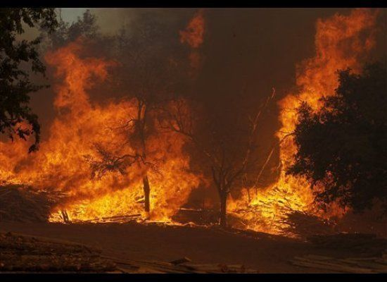 A large wildfire on Highway 71 near Smithville, Texas, burns piles of lumber and ranch posts on September 5