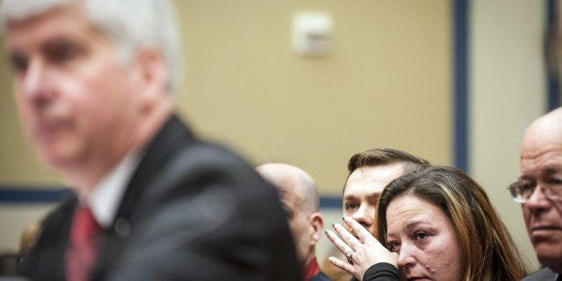 Flint Michigan resident Lee Anne Walters, second from right, reacts as Rick Snyder, governor of Michigan, left, testifies dur