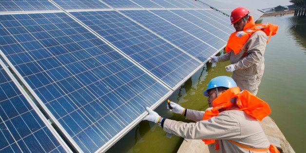 LIANYUNGANG, CHINA - MARCH 16:  (CHINA OUT) Electricians take a boat to inspect the solar panels in a fishing pond on March 1