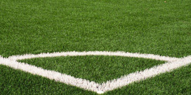 Football playground corner on heated artificial green turf ground with painted white line marks. Milled black rubber in basic