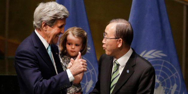 U.S. Secretary of State John Kerry holds his granddaughter Isabel Dobbs-Higginson as he talks to Secretary General Ban Ki-moo