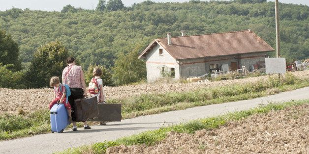 Mother and children wandering through countryside, dragging suitcases behind them