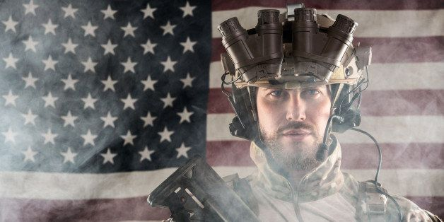 Portrait of Bearded US Army Soldier With Night Vision Goggles on American Flag Background; Smoke Cloud
