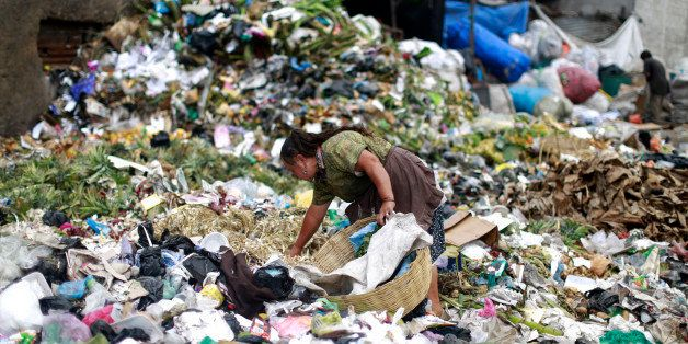 A woman searches for food at the garbage dump of the La Terminal food centre, one of the largest food markets in Guatemala Ci