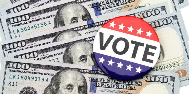 VOTE campaign button on top of scattered hundred dollar bills spread out beneath it. Concept image illustrating election fund