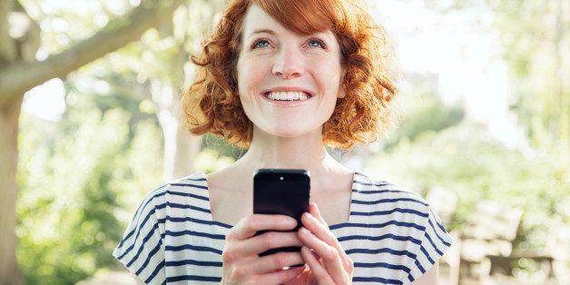 Woman using smart phone outside.