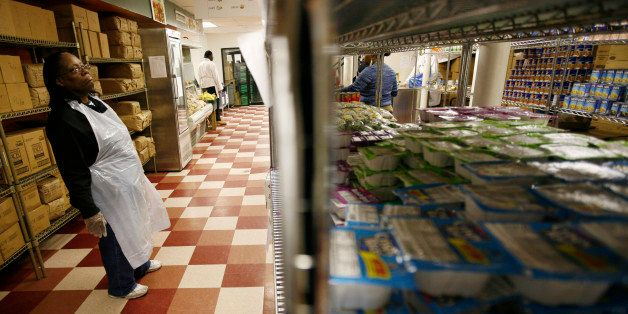 A staff member looks at groceries on shelves at the Community Kitchen food pantry in the Harlem section of New York City Dece
