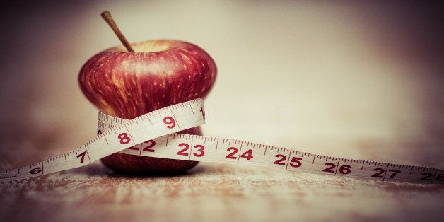 A manipulated photo of an apple squeezed by a measuring tape,  diet, restrictions, weightless, lose weight, health, maintaini