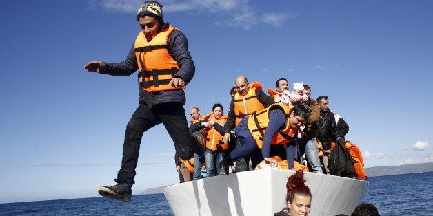 Refugees and migrants jump off a boat as they arrive on the Greek island of Lesbos, November 26, 2015.  REUTERS/Giorgos Mouta