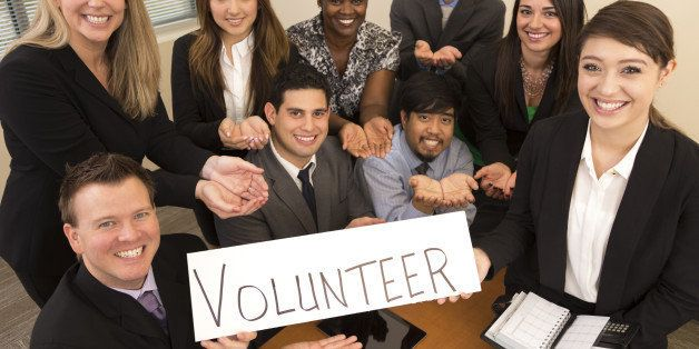 Team of business professionals hold a 'Volunteer' sign with hands cupped to represent the concept of service.
