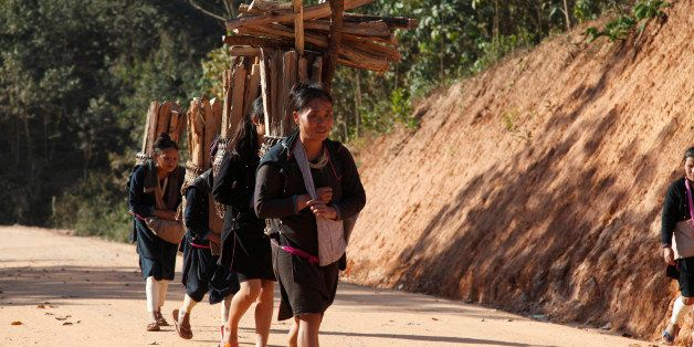 Girls from the Lantan hill tribe carrying wood home along a dust track, wearing traditional dress.