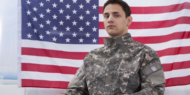 Cropped image of patriotic soldier sitting on wheel chair against American flag