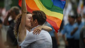 Two women kiss as they take part in the Bucharest Pride 2018 March gay pride parade on June 9, 2018. - The rainbow flag created by artist Gilbert Baker became the symbol of the PRIDE movement 40 years ago, in San Francisco where thousands of people marched on the streets of the city asking respect for lesbians, gays, bisexuals and transgenders. (Photo by Daniel MIHAILESCU / AFP)        (Photo credit should read DANIEL MIHAILESCU/AFP/Getty Images)