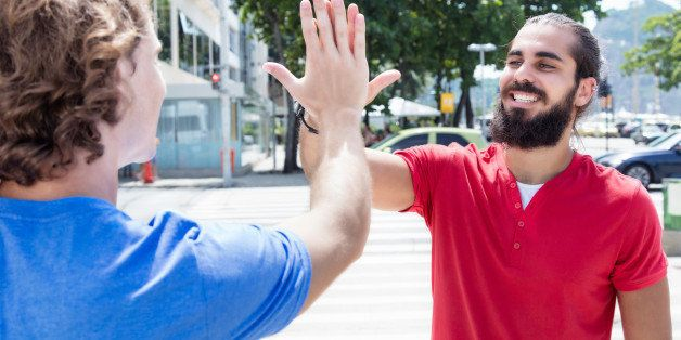 Man with beard give high five to caucasian guy outdoor in the city