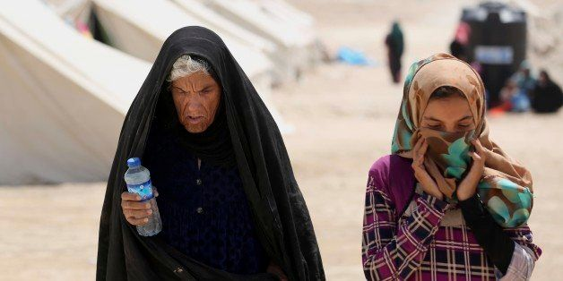 In this picture taken Saturday, June 25, 2016, internally displaced woman and her daughter from Fallujah, who fled their home