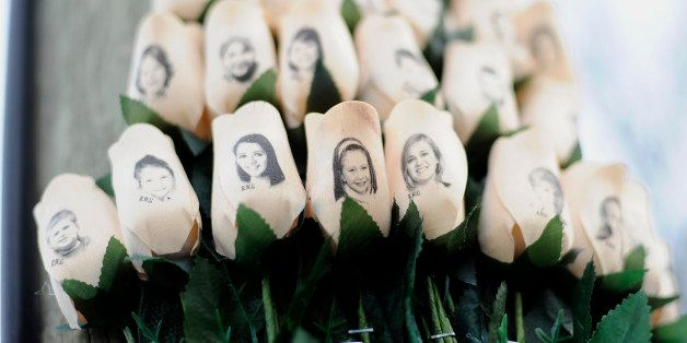 FILE - In this Jan. 14, 2013 file photo, white roses with the faces of victims of the Sandy Hook Elementary School shooting a