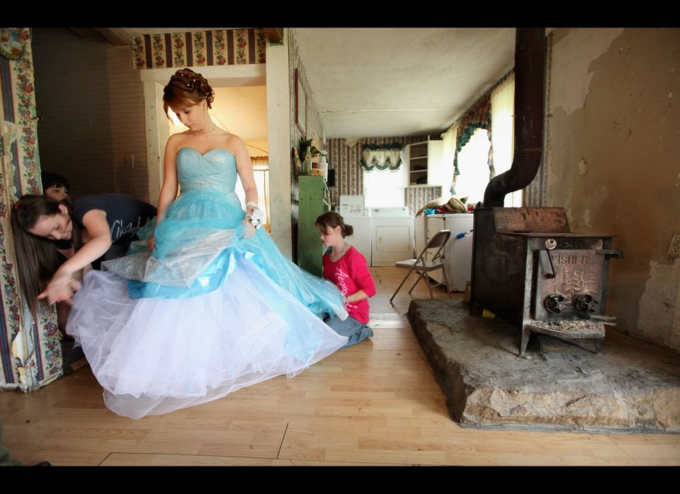 Brittany Brewer fixes her gown as she prepares for the Owsley County High School prom next to a wood stove in the home where