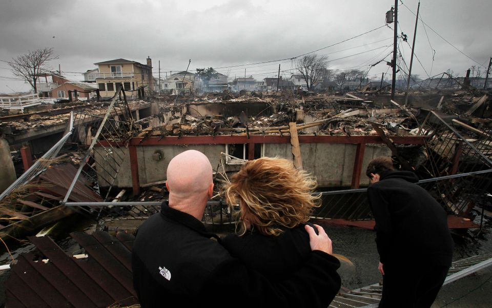 Robert Connolly, left, embraces his wife Laura as they survey the remains of the home owned by her parents that burned to the