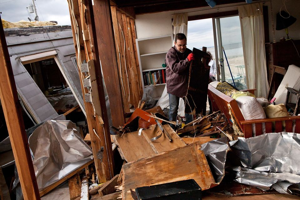 HIGHLANDS, NJ - NOVEMBER 01:  Eric Lenz helps clean out a friend's trailer after it was destroyed by Superstorm Sandy on Nove