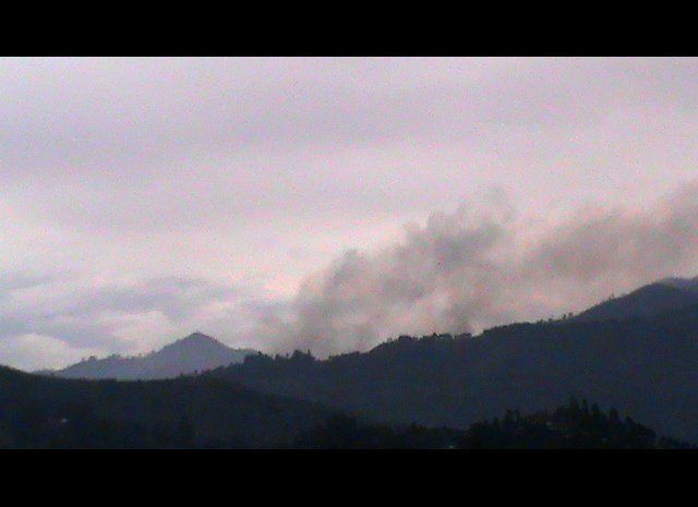 Smoke rises over the mountains as Buabo village burns following an attack on November 11, 2012. The residents of the village