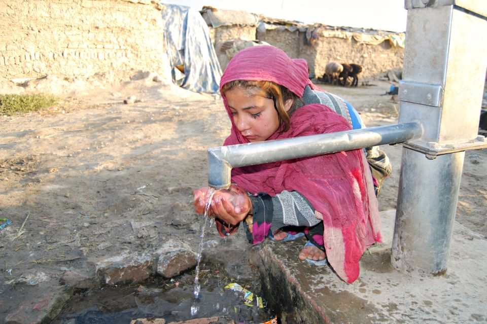 A girl washes prior to going to tent school in a refugee camp on the outskirts of Kabul. Hundreds of one room schools have op