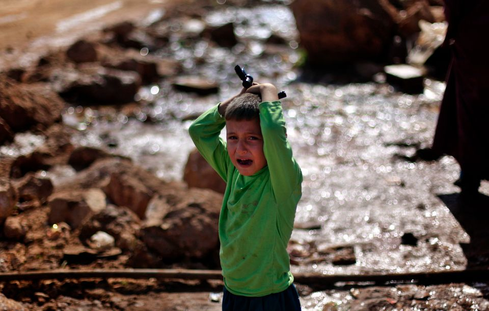 A Syrian boy who fled with his family from the violence in their village, cries as he waits to fill water at a displaced camp