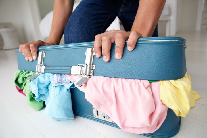 Teenage boy struggling to close suitcase