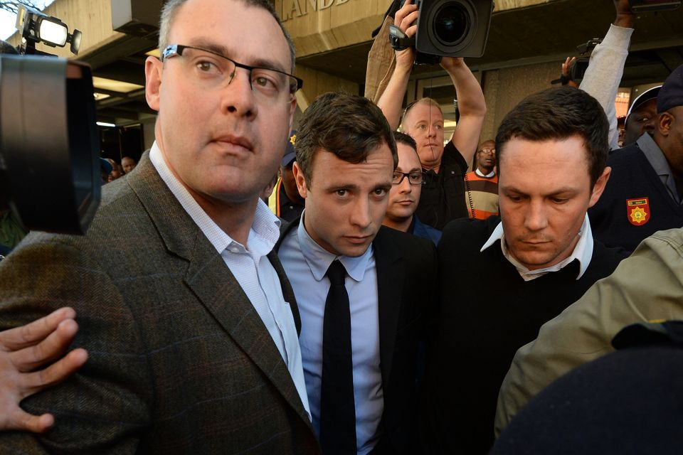 South African Olympic sprinter Oscar Pistorius (C), flanked by bodyguards and policemen, leaves the Magistrate Court in Preto