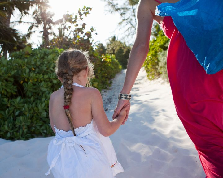 Five year old girl holding her mother's hand while walking in the sand.
