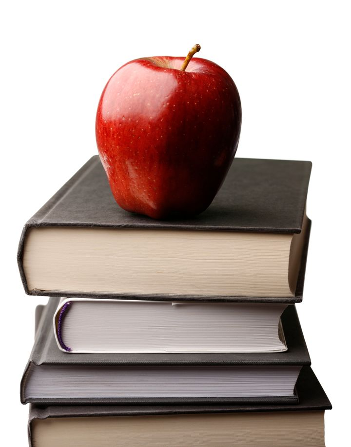 A fresh red delicious apple atop a stack of books with a white background.