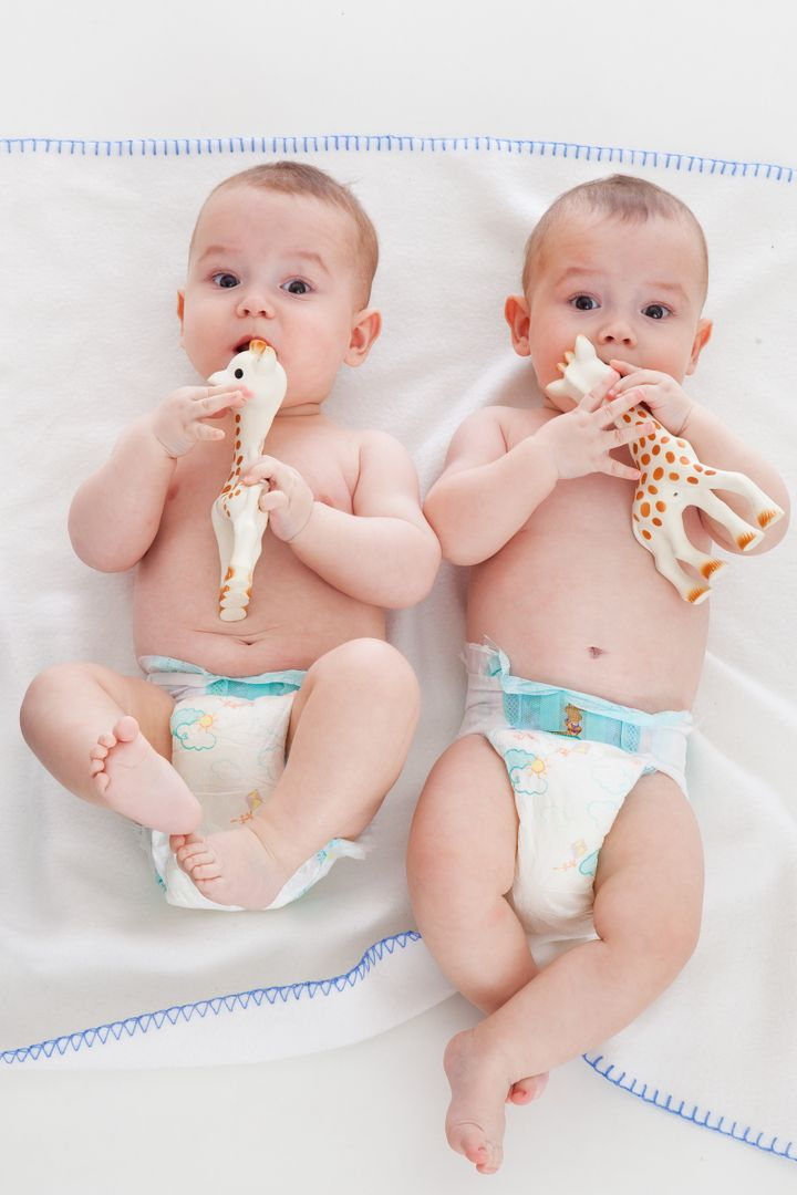 two babies wear diapers and lie on a blanket