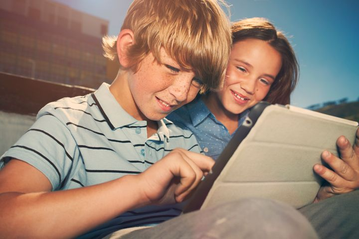 Boy and girl playing with digital tablet
