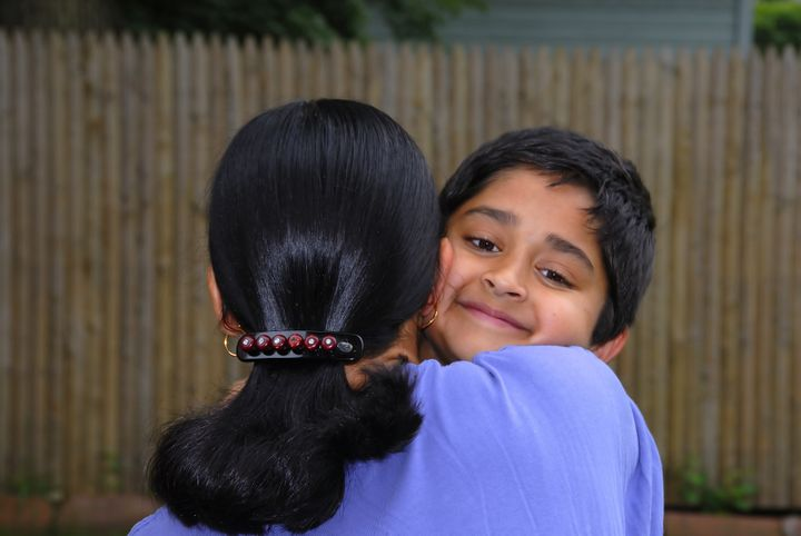 a happy indian kid hugging his...