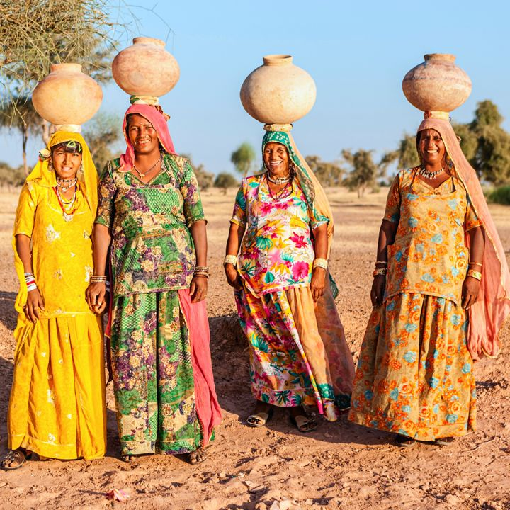 Indian women carrying water from the lake. Collecting and carrying water are women's responsibilities in India. Rajasthani wo