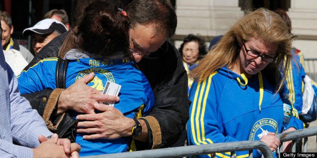 BOSTON, MA - APRIL 16: Runners waiting to pick up their belongings and medals hug the day after two bombs exploded at the fin