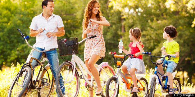 Young happy family riding bicycles outdoors in a park or nature. Making a break to refresh with water. Selective focus to lit