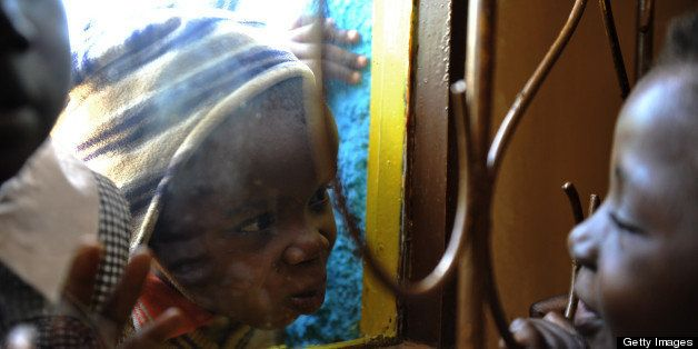 Three-and-a-half year old HIV positive Eugene (C) plays across a window with six-year-old Joan (R) during the last day of cla