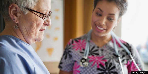 Senior woman discussing prescription medicine with nurse in clinic