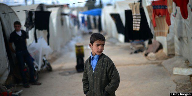An internally displaced Syrian boy stands near tents in the Maiber al-Salam refugee camp along the Turkish border in the nort