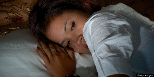 Pretty Asian girl lying on bed with eyes closed.