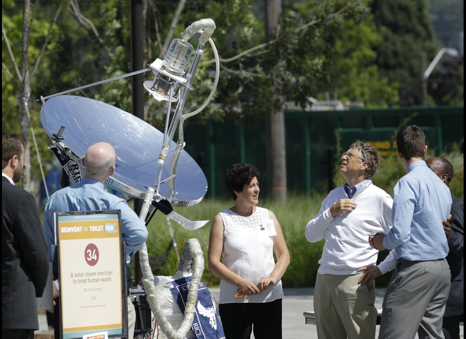 "Bill Gates, third from right, looks at a device that uses solar energy to treat human waste, as he tours the ""Reinventing the"
